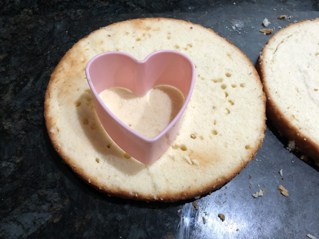 using a cookie cutter to cut out heart shaped cakes