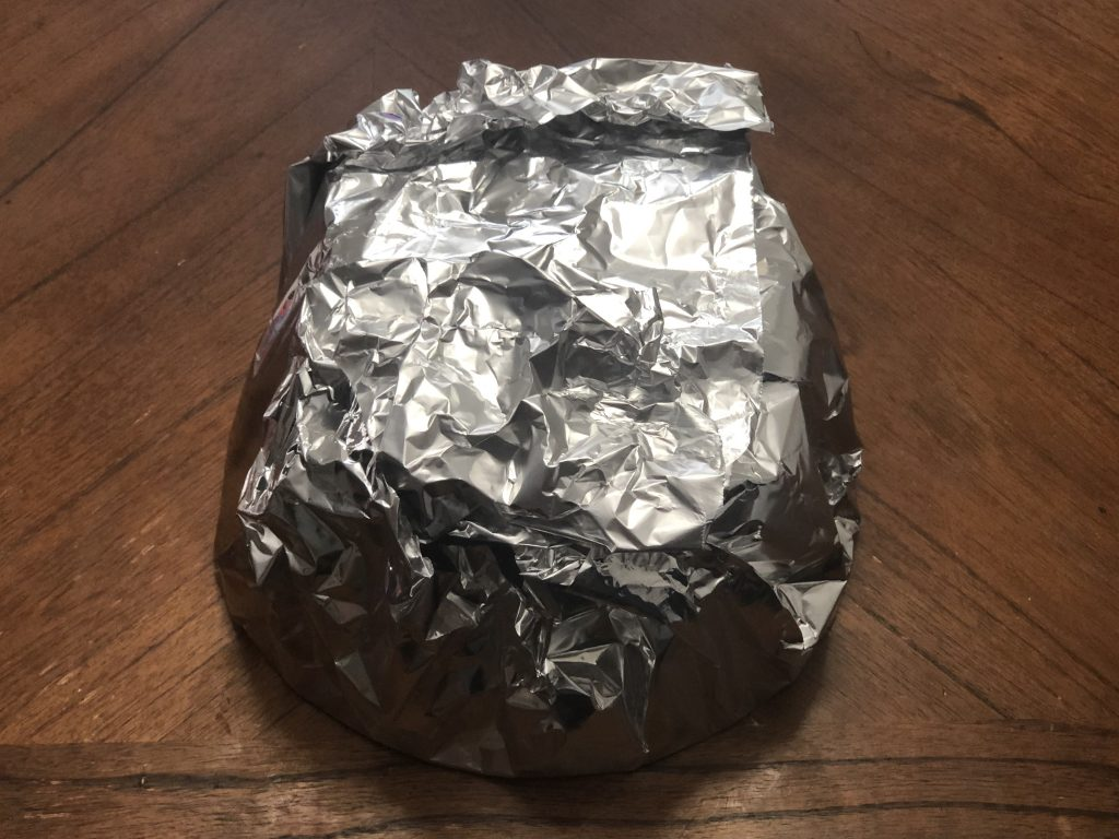 covering a cake in a layer of foil.